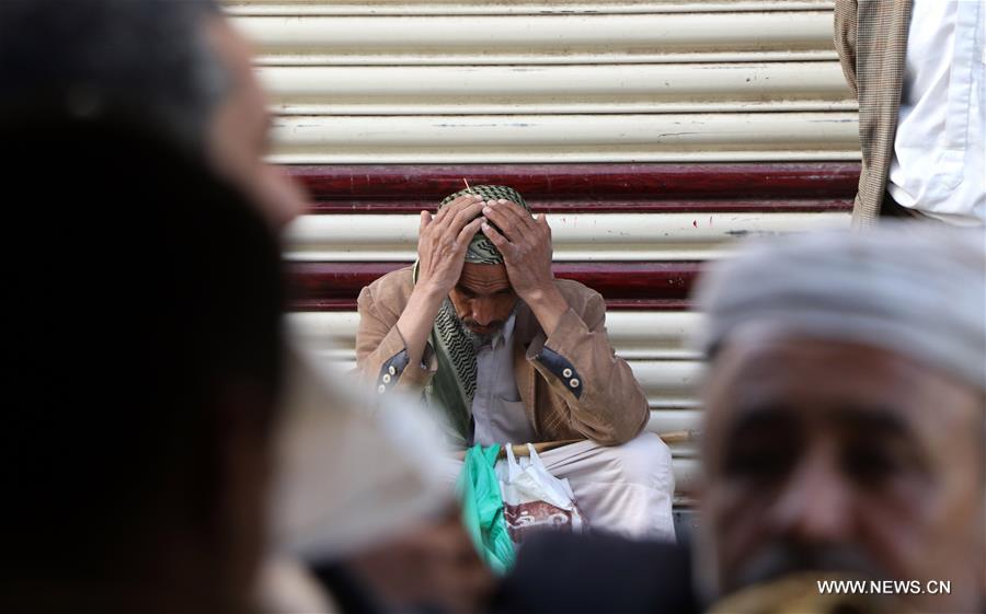 رجل يمني من المتضررين بأكثر من 4 أعوام من الصراعات ينتظر دوره لاستلام خبز مجاني